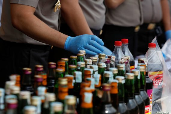Police prepare evidence during a press conference regarding the arrests of suspects linked to the production and sale of illegal bootleg alcohol which claimed the lives of more than 80 people this week in Jakarta